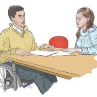 A man, using a wheelchair, and a woman sit at a table with papers in front of them
