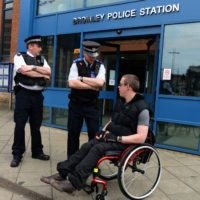 Man in wheelchair with two male police officers outside Bromley Police Station