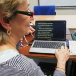 An event attendee using speech-to-text on screen