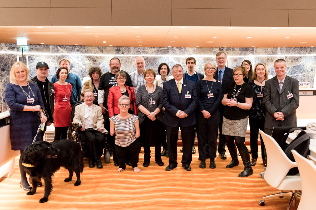 Group photo of twenty disability activists inside UN building in Geneva