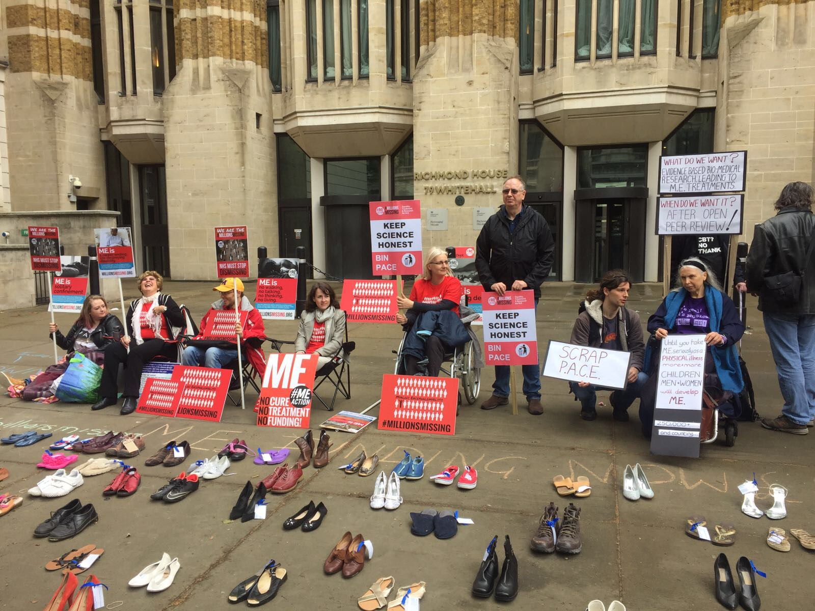 Shoes displayed in front of Whitehall with a group of protestors behind