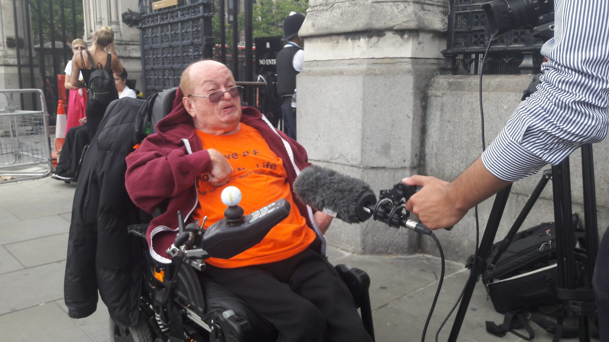 DPAC activist interviewed by a news reporter with microphone outside Parliament