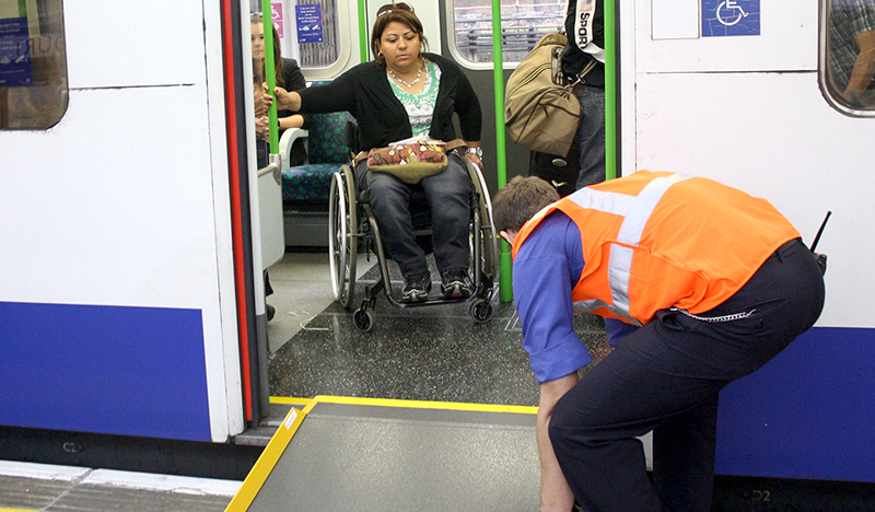 Wheelchair user leaving a tube carriage with assistance from a Transport for London employee