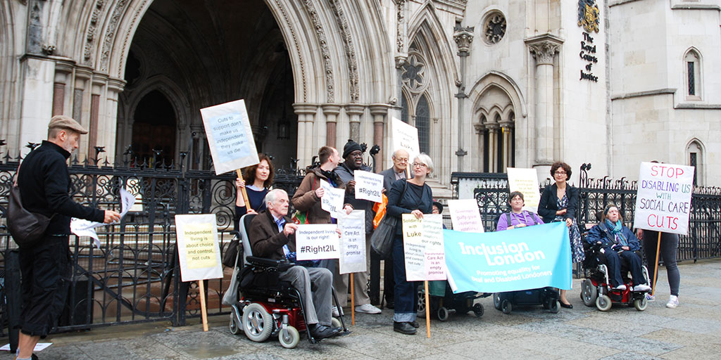 Protesters outside the Royal Courts of Justice with an Inclusion London banner and placards
