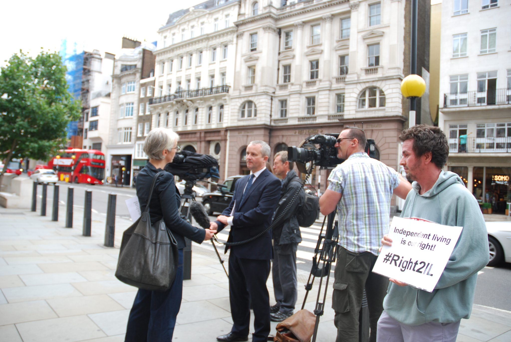 Tracey Lazard interviewed outside the Royal Courts of Justice with a man in the foreground holding a placard reading 'Right2IL'
