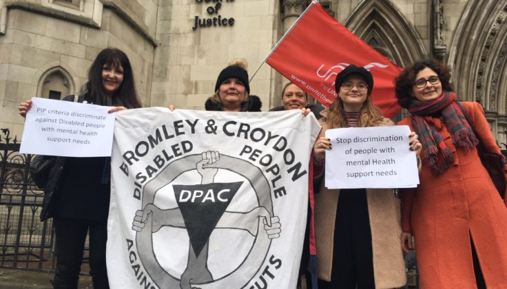 Five protestors outside the Royal Courts of Justice with a Bromley and Croydon DPAC banner
