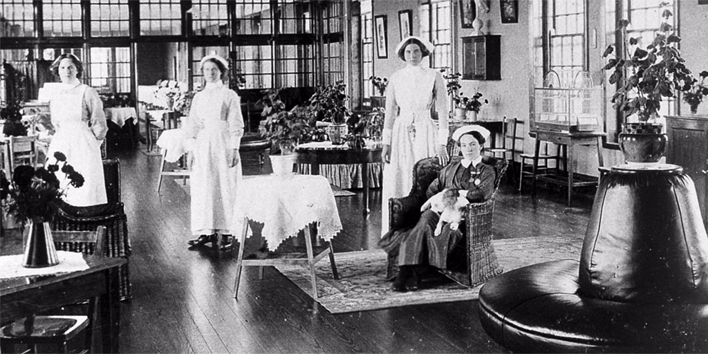 An old black and white photograph of a group of female nurses in white uniforms, in a communal living area in a mental health institution
