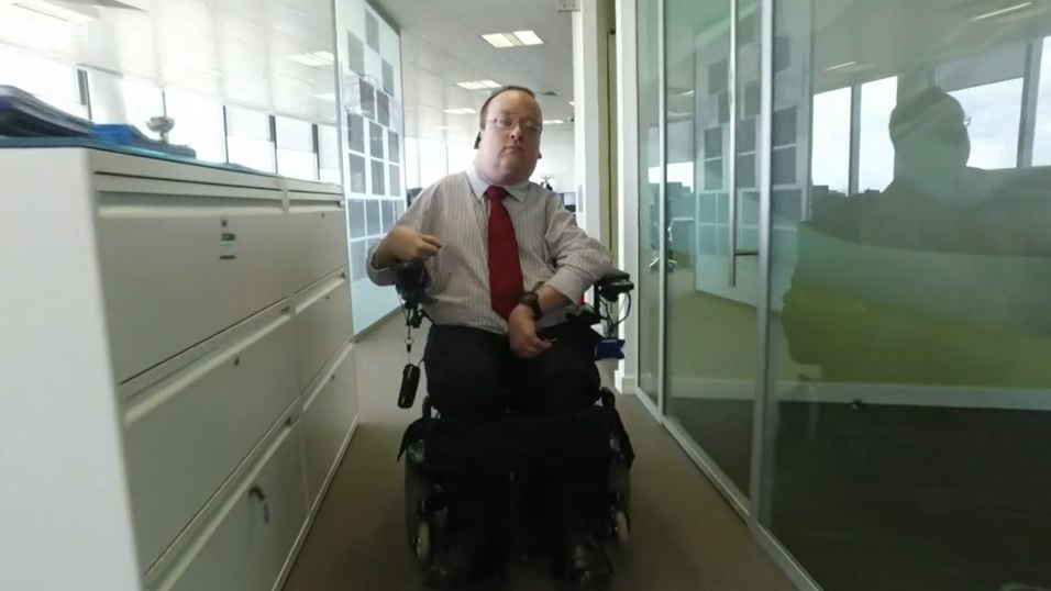 Photo of a male wheelchair user wheeling down the corridor of an office