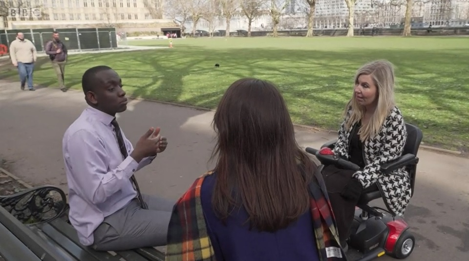 Photo of Paul Ntulila with two women, one of whom is a wheelchair user, having a conversation in a park