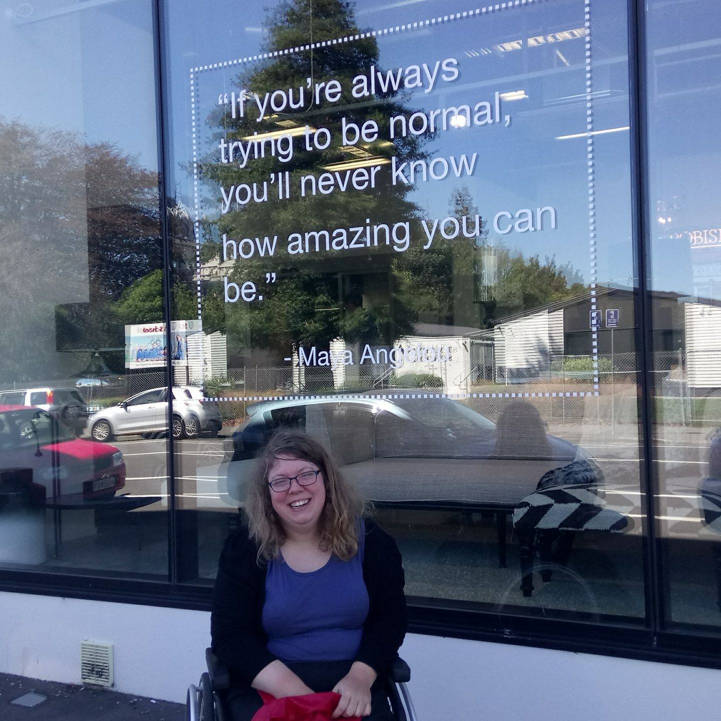 "Zara Todd in front of a window which has written on it ""If you're always trying to be normal, you'll never know how amazing you can be"" - Maya Angelou"
