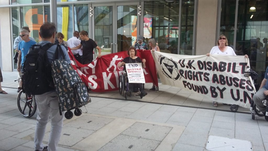 Protesters outside the Global Disability Summit holding banners which say 'UK Disability Rights Abuses Found by U.N.""