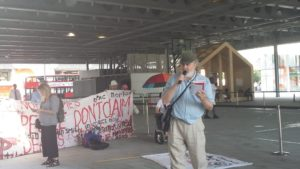 Man speaking outside the Global Disability Summit, in front of a large banner