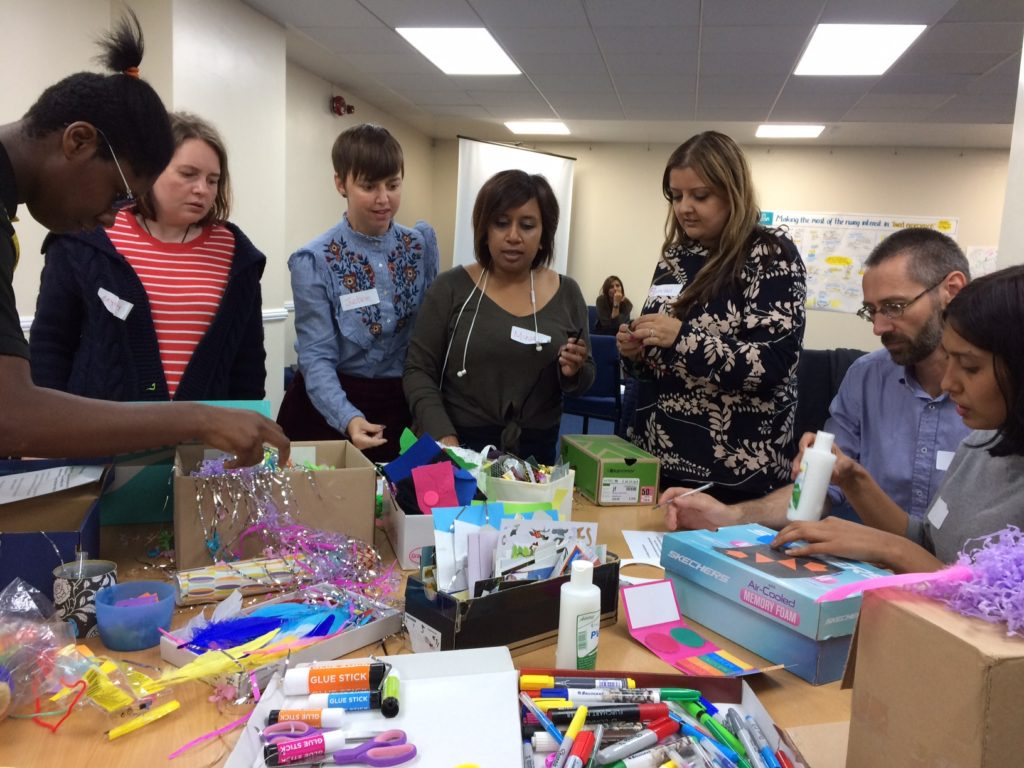 "Picture of 7 people on Inclusion London's leadership programme making ""empathy boxes"" to explore their goals, motivations and fears. They are using a mixture of art materials to design their boxes"