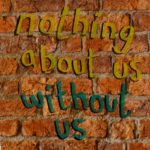 graffiti on a wall reading nothing about us without us